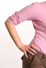 Detail of female torso in pink shirt and yoga pants, hand on hip.