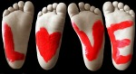 "The soles of four bare feet, with a red letter painted on each: L, heart, V, and E, ""Love."""